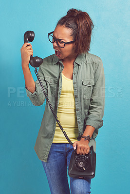 Buy stock photo Shot of a young woman looking irritatedly at a telephone
