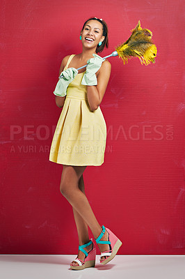 Buy stock photo Studio shot of a young woman holding a feather duster against a red background