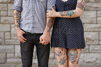 Buy stock photo Cropped shot of a couple with tattoos on their bodies
