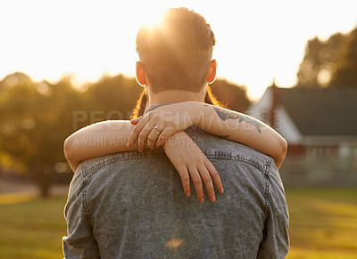 Buy stock photo Shot of an affectionate young couple embracing outdoors