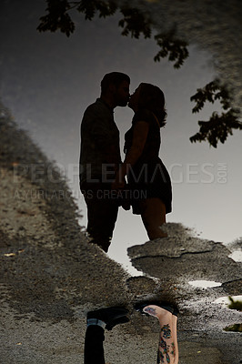 Buy stock photo A reflection of a young affectionate couple in a puddle of water