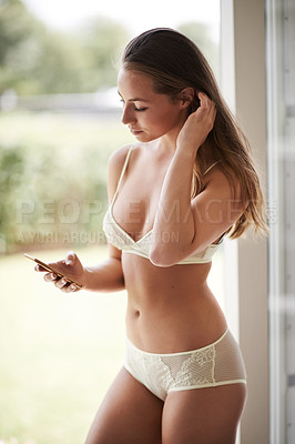 Buy stock photo Shot of a beautiful young woman in her underwear using her cellphone