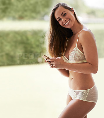 Buy stock photo Portrait of a beautiful young woman in her underwear using her cellphone