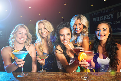 Buy stock photo Shot of young women drinking cocktails in a nightclub
