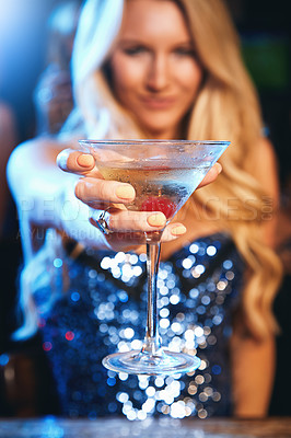 Buy stock photo Shot of a young woman showing you her cocktail in a nightclub