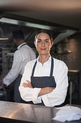 Buy stock photo Cropped portrait of a chef standing with her arms folded in the kitchen