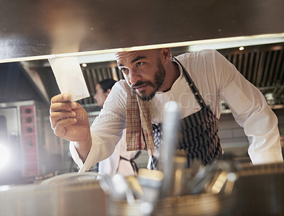 Buy stock photo Shot of a chef looking at an order in the kitchen