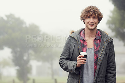 Buy stock photo Cropped portrait of a young man standing outside while drinking a coffee