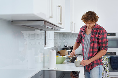 Buy stock photo A young man pouring himself a cup of coffee at home