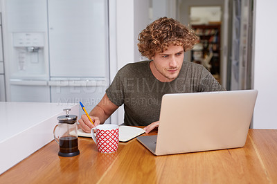 Buy stock photo A young man writing something down in a notebook while sitting with his laptop at home