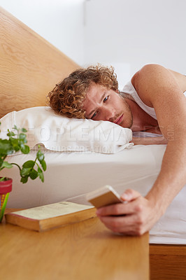 Buy stock photo A young man reaching for his cellphone while lying in bed