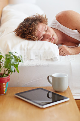 Buy stock photo A young man lying in bed with his tablet and a coffee cup on his bedside table