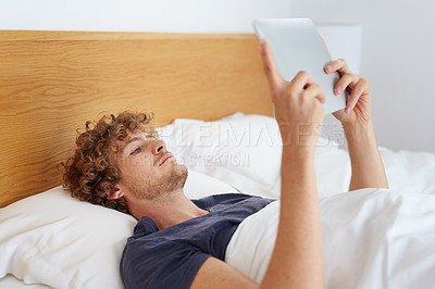 Buy stock photo Shot of a young man using his digital tablet while lying in bed