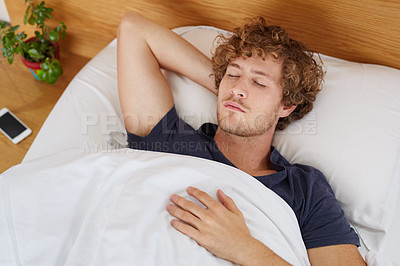Buy stock photo Shot of a young man sleeping in his bed
