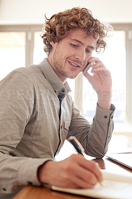 Buy stock photo Cropped portrait of a young businessman writing notes while while making a call at home