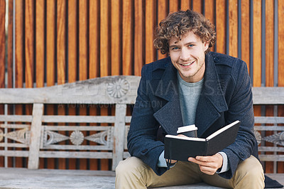 Buy stock photo Cropped portrait of a young man drinking coffee and reading his diary while sitting on a bench outside