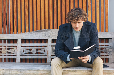 Buy stock photo Cropped shot of a young man drinking coffee and reading his diary while sitting on a bench outside