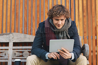 Buy stock photo Cropped shot of a young man using his tablet while sitting on a bench outside