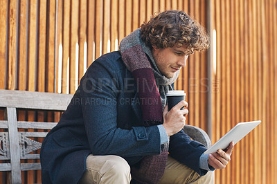 Buy stock photo Cropped shot of a young man drinking coffee and using his tablet while sitting on a bench outside