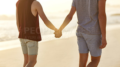 Buy stock photo Cropped rearview shot of a young couple walking along the beach