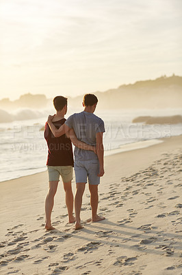 Buy stock photo Shot of a young couple walking arm in arm along the beach