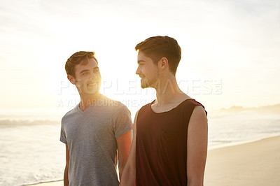 Buy stock photo Shot of a young couple walking on the beach