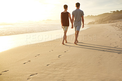 Buy stock photo Rearview shot of a young couple walking along the beach