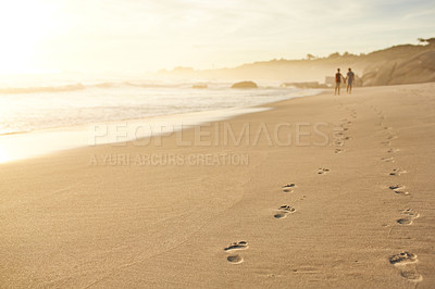 Buy stock photo Shot of footprints in the sand at the beach with a couple walking in the distance