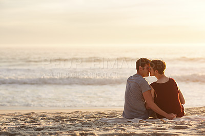 Buy stock photo Rearview shot of an affectionate young couple sitting on the beach