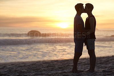 Buy stock photo Shot of a young couple kissing on the beach at sunset
