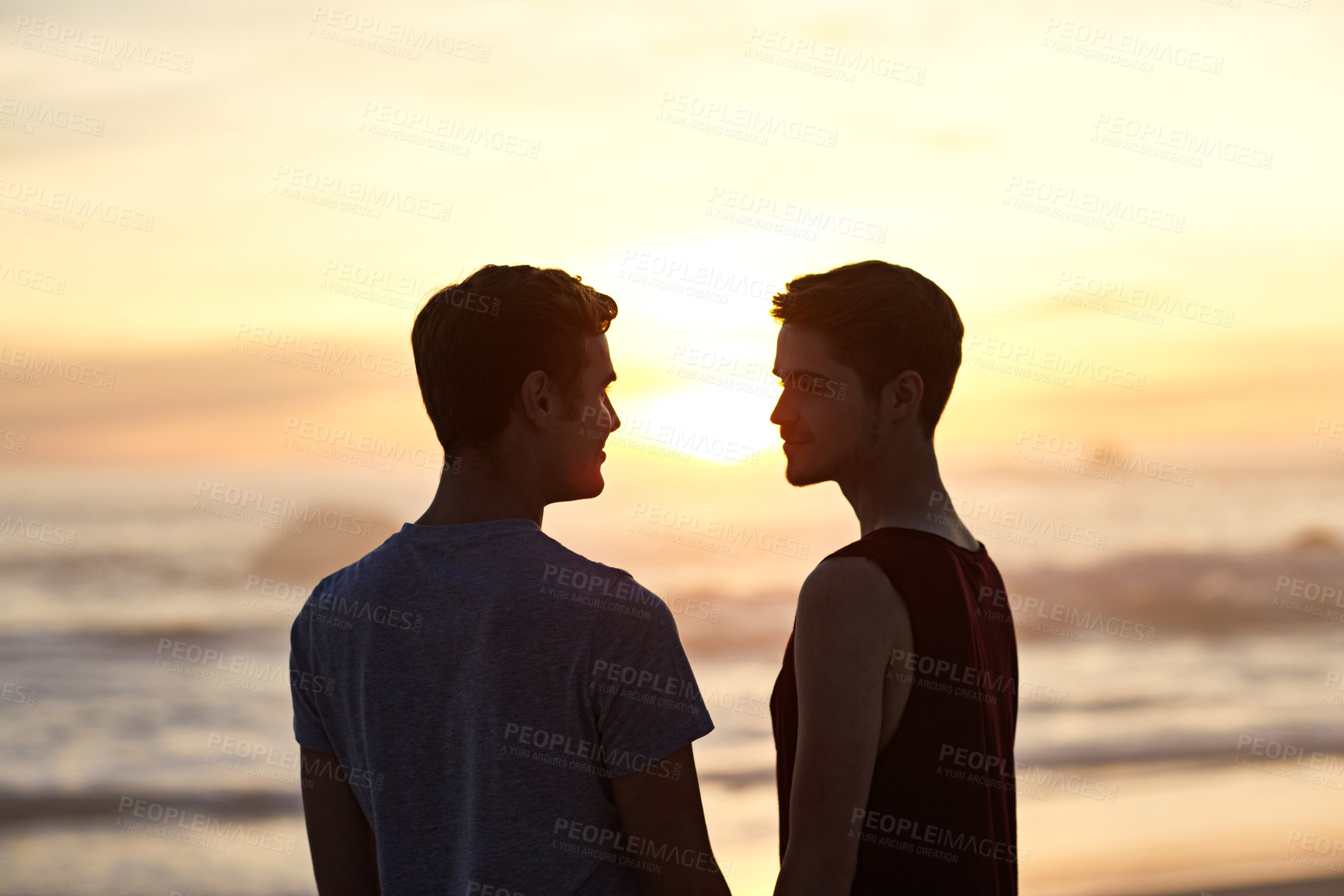 Buy stock photo Cropped shot of a young couple on the beach at sunset