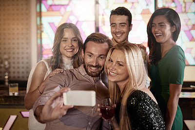 Buy stock photo Shot of a group of friends taking a selfie in a bar