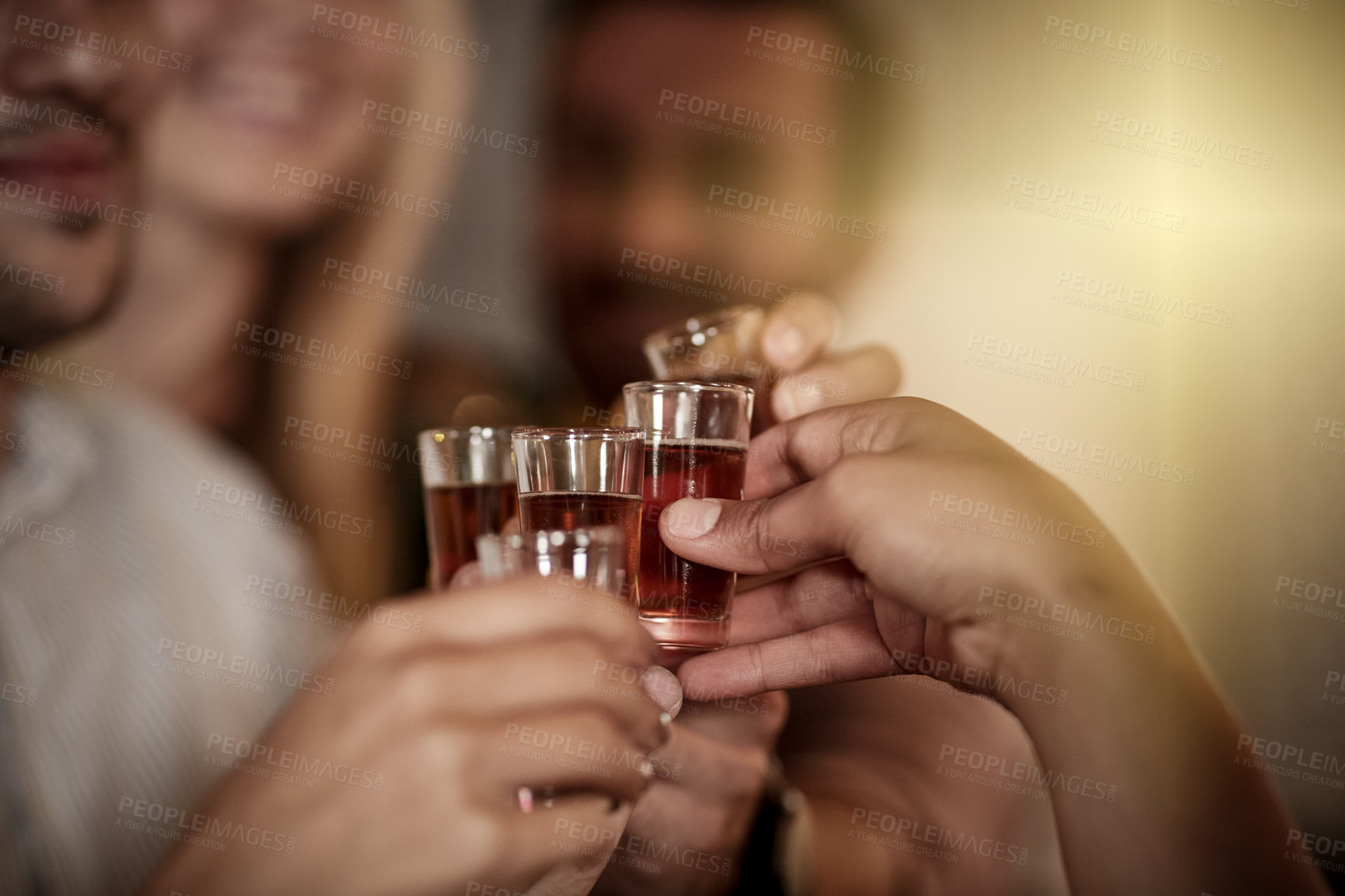 Buy stock photo Cropped shot of a group of friends toasting before they down their shot