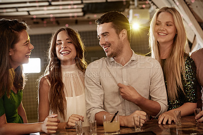 Buy stock photo Shot of a group of friends enjoying drinks at the bar