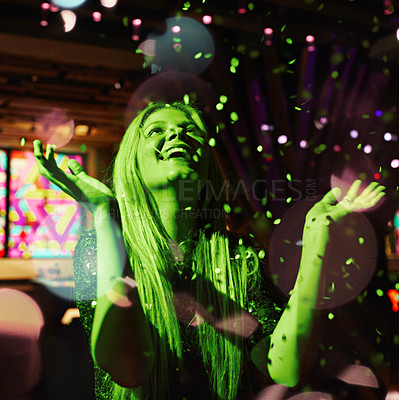 Buy stock photo Shot of a young woman enjoying herself in the confetti in a nightclub