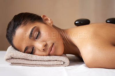 Buy stock photo A young woman receiving a hot stone treatment at a spa