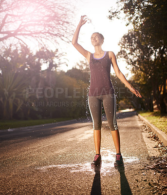 Buy stock photo Shot of a young woman pouring cold water over her head after an intense workout