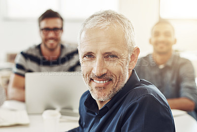 Buy stock photo Portrait of a mature office worker sitting at a table with colleagues in the background