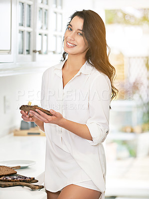Buy stock photo Shot of a young woman enjoying breakfast in her kitchen