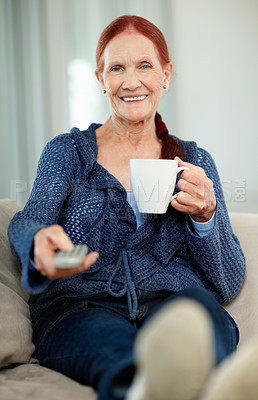 Buy stock photo Portrait of a happy mature woman holding a cup of tea or coffee while watching television