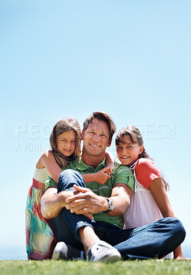 Buy stock photo Full length of man sitting on grass with his daughters and smiling - copyspace