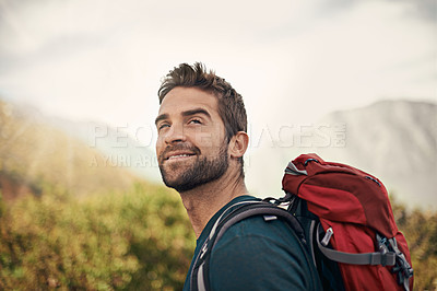 Buy stock photo Shot of a young man enjoying a hike through the mountains