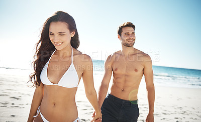 Buy stock photo Shot of a young couple going for a walk along the beach