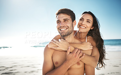 Buy stock photo Shot of a young couple enjoying a piggyback ride at the beach