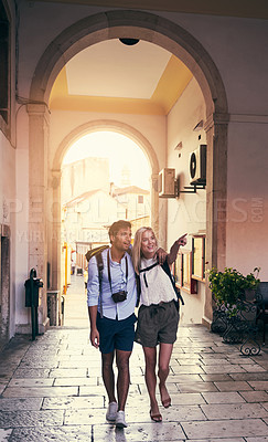 Buy stock photo Full length shot of a young couple working through a foreign city