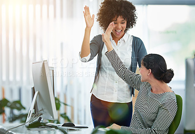 Buy stock photo Shot of designers hi-fiving together at a workstation in an office