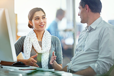 Buy stock photo Shot of designers talking together at a workstation in an office