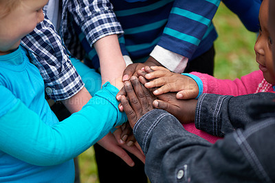 Buy stock photo Shot of a diverse group of children standing with their hands together
