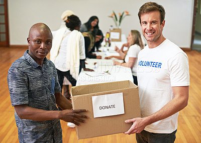 Buy stock photo Cropped portrait of two volunteers carrying a donations box