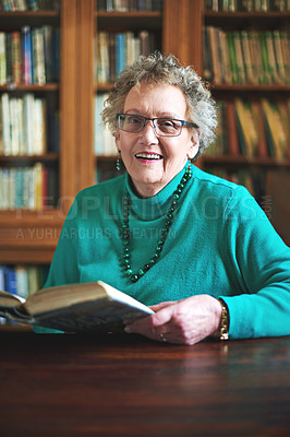 Buy stock photo Portrait of a smiling senior woman sitting at a table reading